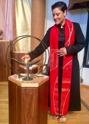 Rev. Rebekah A. Savage lighting a flaming chalice.